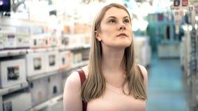 Όμορφη ελκυστική νέα γυναίκα στο κατάστημα Πιό chandilier τμήμα λαμπτήρων Έννοια καταναλωτισμού απόθεμα βίντεο