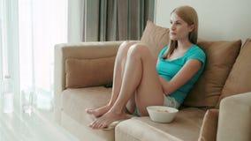 Όμορφη ελκυστική συνεδρίαση γυναικών στον κινηματογράφο καναπέδων και προσοχής Κατανάλωση των τσιπ από το άσπρο κύπελλο φιλμ μικρού μήκους