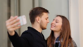 Όμορφη ελκυστική χαμογελώντας γυναίκα που παίρνει selfies με τον όμορφο φίλο της στο τηλέφωνό της απόθεμα βίντεο