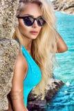 Όμορφη ζαλίζοντας προκλητική ξανθή γυναίκα στα γυαλιά ηλίου και τα κομψά ενδύματα και μπικίνι γύρω από τη λίμνη Στοκ Φωτογραφίες