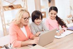 Όμορφη ηλικιωμένη δακτυλογράφηση γυναικών στο lap-top με τα εγγόνια της στοκ εικόνα
