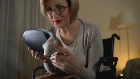 Όμορφη ηλικιωμένη κυρία που εφαρμόζει το φωτεινό κραγιόν και που φαίνεται καθρέφτης, που υπενθυμίζει τη νεολαία απόθεμα βίντεο