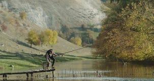Όμορφη ηλιόλουστη ημέρα ένα άτομο που πιάνει τα ψάρια από τη λίμνη, στέκεται επάνω σε μια γέφυρα απόθεμα βίντεο