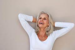 Όμορφη ηλικιωμένη γυναίκα που κλίνει με τα χέρια πίσω από το κεφάλι Στοκ Εικόνες