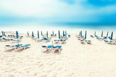 Όμορφη ηλιόλουστη ακτή παραλιών με τις καρέκλες και δέκα σαλονιών παραλιών Στοκ εικόνα με δικαίωμα ελεύθερης χρήσης