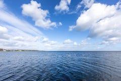 Όμορφη θάλασσα κάτω από το νεφελώδη μπλε ουρανό Στοκ Φωτογραφίες