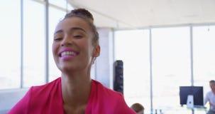 Όμορφη θηλυκή εκτελεστική στάση αναμιγνύω-φυλών στο σύγχρονο γραφείο 4k απόθεμα βίντεο