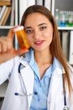 Όμορφη θηλυκή λαβή γιατρών στο μπουκάλι χαπιών όπλων Στοκ Εικόνες