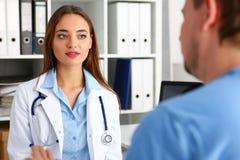 Όμορφη θηλυκή συζήτηση γιατρών με τον αρσενικό επισκέπτη Στοκ Εικόνες