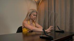 Όμορφη θηλυκή σύνδεση με τη διαφανή επίδειξη υπολογιστών γυαλιού φιλμ μικρού μήκους