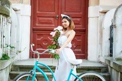 Όμορφη θηλυκή τοποθέτηση με τα λουλούδια κοντά στο μπλε ποδήλατο μπροστά από το όμορφο μέρος στοκ φωτογραφία με δικαίωμα ελεύθερης χρήσης