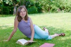 Όμορφη θηλυκή εφηβική ανάγνωση ένα βιβλίο στη χλόη Στοκ Εικόνα