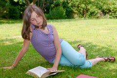 Όμορφη θηλυκή εφηβική ανάγνωση ένα βιβλίο στη χλόη Στοκ εικόνα με δικαίωμα ελεύθερης χρήσης