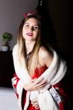Όμορφη θηλυκή προκλητική γυναίκα νοσοκόμων στο κοστούμι καρναβαλιού, στους ώμους της ένα κόκκινο παλτό γουνών Στοκ Φωτογραφίες