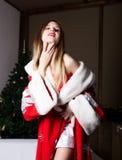 Όμορφη θηλυκή προκλητική γυναίκα νοσοκόμων στο κοστούμι καρναβαλιού, στους ώμους της ένα κόκκινο παλτό γουνών Στοκ Φωτογραφία