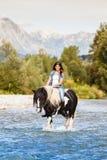Όμορφη θηλυκή συνεδρίαση στο άλογο διασχίζοντας το ρ Στοκ εικόνα με δικαίωμα ελεύθερης χρήσης