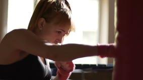 Όμορφη ισχυρή γυναίκα που χτυπά punchbag σκληρά, παίρνοντας την μόνος-αμυντική σειρά μαθημάτων φιλμ μικρού μήκους