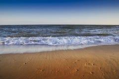 Όμορφη κίτρινη αμμώδης παραλία κοντά στην μπλε θάλασσα Στοκ Φωτογραφία