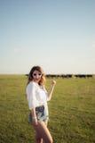 Όμορφη και γυναίκα μόδας στον πράσινο τομέα που δείχνει με το χέρι της στοκ εικόνες με δικαίωμα ελεύθερης χρήσης