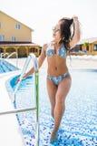 Όμορφη και ελκυστική νέα γυναίκα που στέκεται σε μια πισίνα Στοκ Φωτογραφία