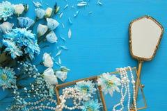 όμορφη και λεπτή μπλε ρύθμιση λουλουδιών δίπλα στο περιδέραιο μαργαριταριών και τον καθρέφτη χεριών Στοκ εικόνα με δικαίωμα ελεύθερης χρήσης