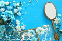 όμορφη και λεπτή μπλε ρύθμιση λουλουδιών δίπλα στο περιδέραιο μαργαριταριών και τον καθρέφτη χεριών Στοκ φωτογραφίες με δικαίωμα ελεύθερης χρήσης