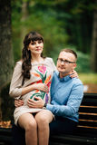 Όμορφη και ευτυχής έγκυος χαλάρωση ζευγών έξω στη συνεδρίαση πάρκων φθινοπώρου στον πάγκο Στοκ Εικόνα