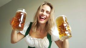 Όμορφη και εύθυμη σερβιτόρα στα παραδοσιακά γερμανικά γυαλιά μπύρας εκμετάλλευσης κοστουμιών στο άσπρος-δόντι-χαμόγελο Oktoberfes απόθεμα βίντεο