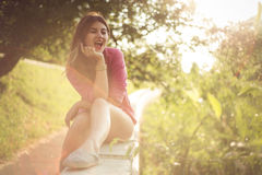 Όμορφη και ελκυστική συνεδρίαση γυναικών σε μια πλευρά, που φορά τα προκλητικά περιστασιακά σορτς τζιν στοκ φωτογραφία με δικαίωμα ελεύθερης χρήσης