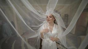 Όμορφη και καλή νύφη στην εσθήτα νύχτας κάτω από το τεράστιο πέπλο Γαμήλιο πρωί απόθεμα βίντεο