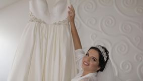 Όμορφη και καλή νύφη στην εσθήτα και το πέπλο νύχτας γάμος κατάταξης τεμαχίων φορεμάτων κίνηση αργή απόθεμα βίντεο