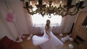 Όμορφη και καλή νύφη στο γαμήλιο φόρεμα που χορεύει κοντά στο παράθυρο Γαμήλιο πρωί Αρκετά και καλά-καλλωπισμένη γυναίκα κίνηση α φιλμ μικρού μήκους