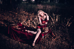 Όμορφη και κομψή ξανθή γυναίκα με τα κόκκινα χείλια και τα κύματα τρίχας που φορούν την κόκκινη τοποθέτηση nightie κρασιού στο φθ Στοκ Εικόνες