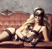 Όμορφη και νέα τοποθέτηση γυναικών προκλητικό lingerie και το ενετικό μ Στοκ Εικόνα