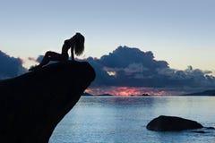 Όμορφη και προκλητική σκιαγραφία σωμάτων γυναικών στο βράχο, στο ηλιοβασίλεμα Στοκ φωτογραφία με δικαίωμα ελεύθερης χρήσης