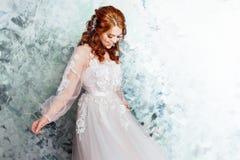 Όμορφη και ρομαντική νύφη στο γαμήλιο φόρεμα με τα μακριά μανίκια Νέα κοκκινομάλλης γυναίκα στο γαμήλιο φόρεμα Στοκ Εικόνα