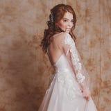 Όμορφη και ρομαντική νύφη στο γαμήλιο φόρεμα με τα μακριά μανίκια Νέα κοκκινομάλλης γυναίκα στο γαμήλιο φόρεμα Στοκ Εικόνες