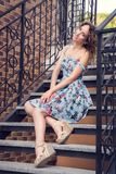 Όμορφη καλά-καλλωπισμένη γυναίκα σε μια μπλε τοποθέτηση φορεμάτων στα σκαλοπάτια με τα στριμμένα κιγκλιδώματα στοκ εικόνα με δικαίωμα ελεύθερης χρήσης