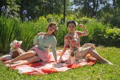 Όμορφη καρφίτσα δύο επάνω στις κυρίες που έχουν το συμπαθητικό πικ-νίκ στο πάρκο πόλεων σε μια ηλιόλουστη ημέρα από κοινού οι φίλ στοκ φωτογραφίες