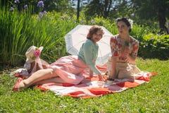 Όμορφη καρφίτσα δύο επάνω στις κυρίες που έχουν το συμπαθητικό πικ-νίκ στο πάρκο πόλεων σε μια ηλιόλουστη ημέρα από κοινού οι φίλ στοκ φωτογραφία με δικαίωμα ελεύθερης χρήσης