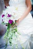 Όμορφη κατάλληλη νύφη με την άσπρη και πορφυρή ανθοδέσμη Στοκ Φωτογραφίες