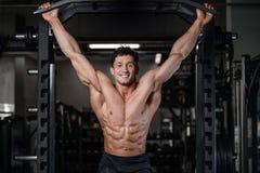 Όμορφη κατάρτιση bodybuilder στους προκλητικούς αλτήρες ανελκυστήρων ατόμων γυμναστικής Στοκ Φωτογραφίες