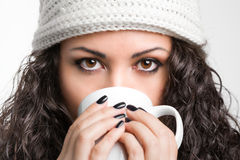Όμορφη κατανάλωση brunette από μια κούπα Στοκ Φωτογραφία