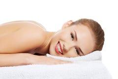 Όμορφη καυκάσια γυμνή γυναίκα που βρίσκεται σε έναν πίνακα μασάζ και rel στοκ εικόνες