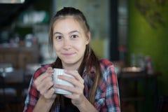 Όμορφη καυκάσια γυναίκα που κρατά ένα φλιτζάνι του καφέ στο χέρι της στοκ εικόνα