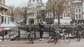 Όμορφη καυκάσια γυναίκα που τελειώνει ένα τηλεφώνημα Συζητήσεις φωτογράφων οδών στο φίλο της στη γέφυρα ποταμών με τα ποδήλατα 4K απόθεμα βίντεο