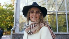 Όμορφη καυκάσια γυναίκα στο μοντέρνο καπέλο που κοιτάζει στη κάμερα και που φορά τα γυαλιά ηλίου στο πάρκο Κλείστε αυξημένος απόθεμα βίντεο