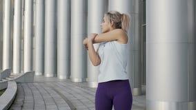 Όμορφη καυκάσια γυναίκα sportswear που τεντώνει αργά τα όπλα, που θερμαίνουν το σώμα φιλμ μικρού μήκους