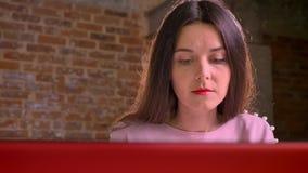 Όμορφη καυκάσια κυρία που εργάζεται στο lap-top της με τη συγκέντρωση εσωτερική απόθεμα βίντεο