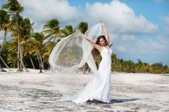 Όμορφη καυκάσια τοποθέτηση νυφών σε μια τροπική παραλία στοκ εικόνες